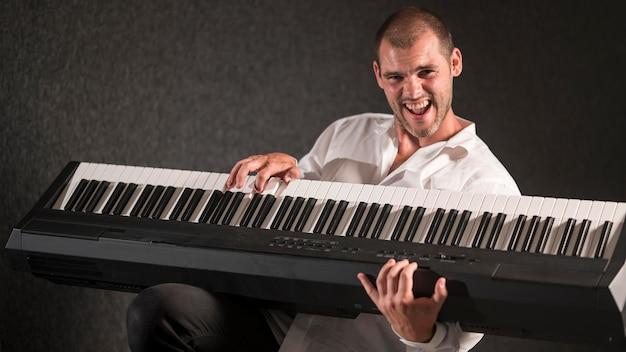 Artysta w białej koszuli trzyma i gra na klawiszach