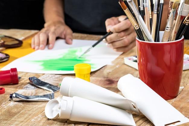 Artysta w studio z farbą i pędzlami
