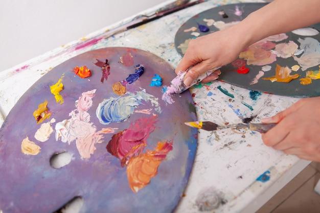 Artysta wyciska farbę olejną na paletę