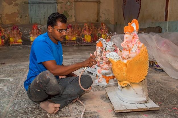 Artysta wykonujący posąg i wykańczający posąg hinduskiego boga pana ganeszy w warsztacie artystycznym na festiwal ganesha.