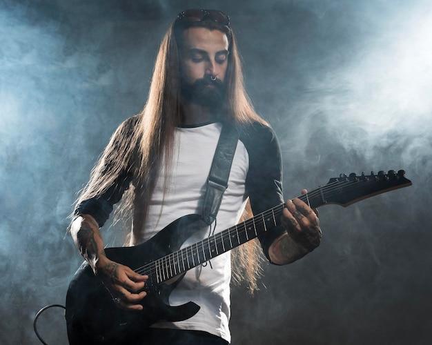 Artysta z długimi włosami gra na gitarze