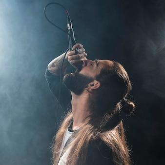 Artysta z długimi włosami śpiewa na scenie