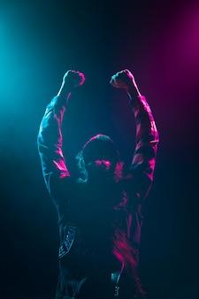Artysta z długimi włosami, trzymając się za ręce w powietrzu na scenie