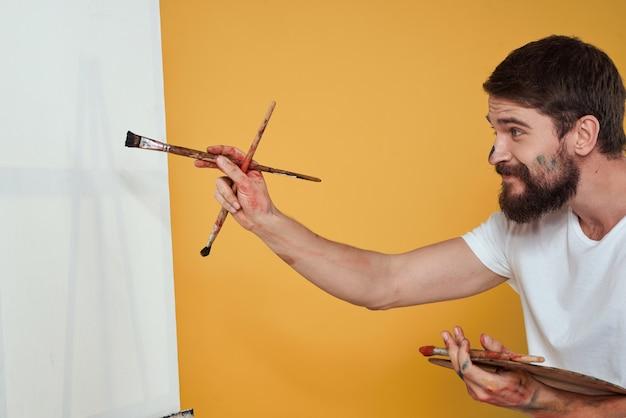 Artysta z malarstwa palety i sztalugi na białym tle