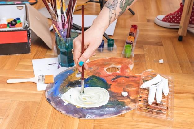 Artysta zanurza pędzel w farbie