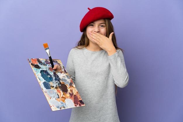 Artystka dziewczyna na białym tle szczęśliwa i uśmiechnięta zakrywająca usta dłonią mouth