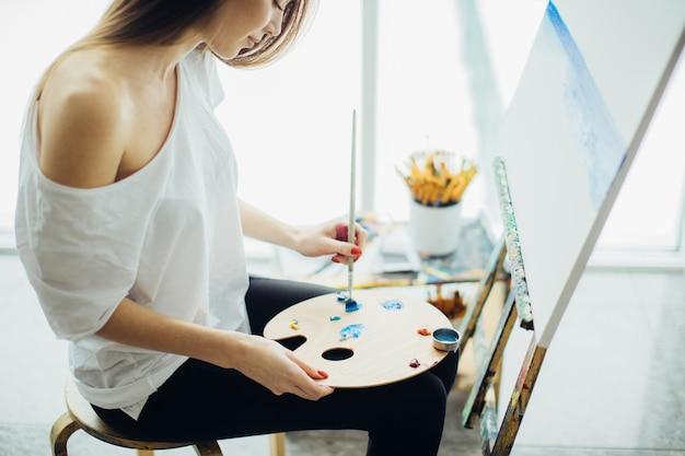 Artystka malująca obraz w dobrze oświetlonym studiu