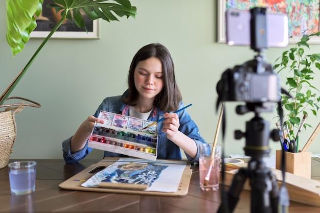Artystka maluje akwarelami i tworzy filmy na swoim blogu na swoim kanale. dziewczyna pokazująca co przyciąga i ucząca swoich naśladowców, dzieci i młodzież. szkolenie, edukacja, kierownictwo artystyczne