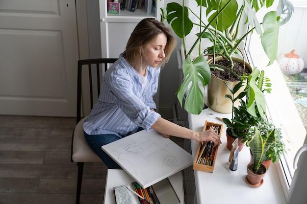 Artystka maluje obraz na płótnie i robi szkice ołówkiem siedząc przy oknie
