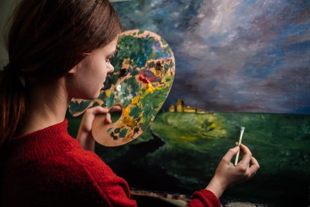 Artystka maluje obraz pędzlem na sztaludze