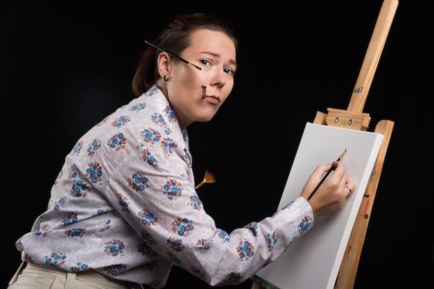 Artystka maluje ołówkiem na czarnym tle obraz na płótnie