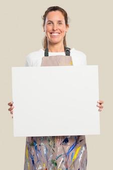 Artystka pokazująca białe płótno z przestrzenią projektową