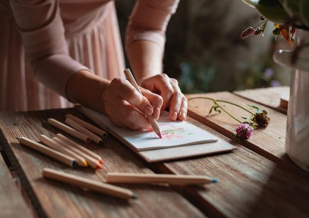 Artystka rysuje kompozycję dzikich kwiatów w doniczce