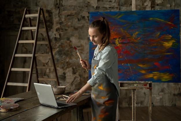 Artystka rysuje obrazek i prowadzi zdalne zajęcia z rysunku. kobieta pokazuje, że rysuje i uczy swoich uczniów