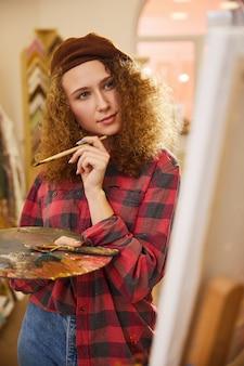 Artystka trzyma pędzel i patrzy na swoją pracę