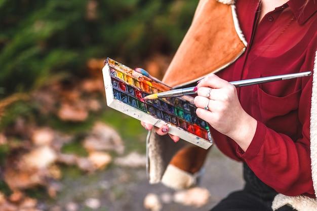 Artystka trzyma w dłoni farby akwarelowe.