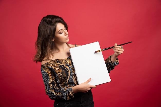 Artystka trzymająca swoje dzieło na płótnie i demonstrując ją publicznie.