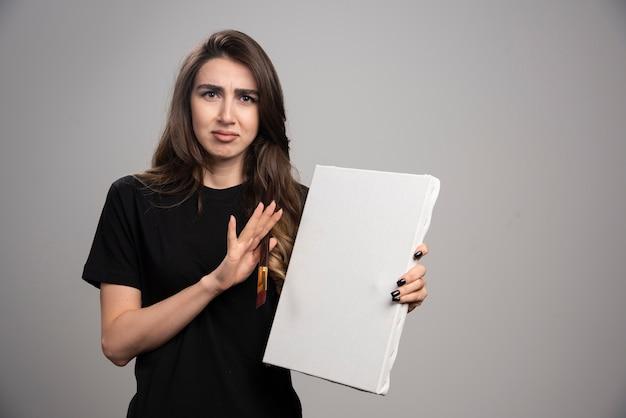 Artystka w czarnej koszuli pozuje z pędzlem i płótnem.