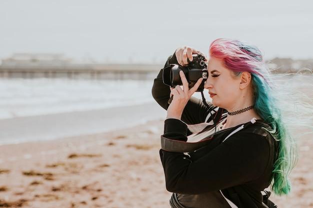 Artystyczna kobieta robi zdjęcie na plaży
