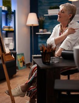 Artystyczna starsza kobieta pracująca nad arcydziełem w pracowni artystycznej