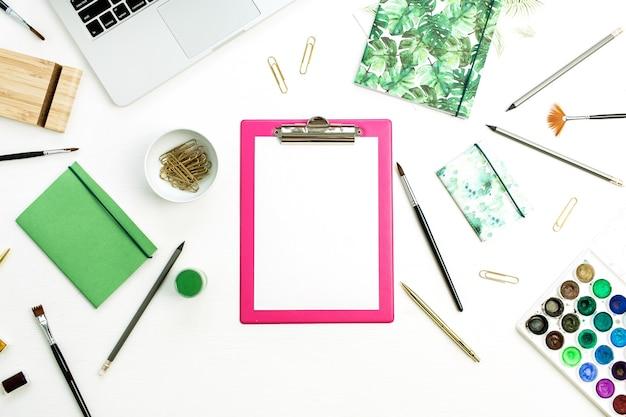 Artystyczne biurko do pracy w domu ze schowkiem, laptopem, notatnikiem, akwarelą i papeterią. koncepcja bloga widoku płaskiego świeckich, widok z góry.
