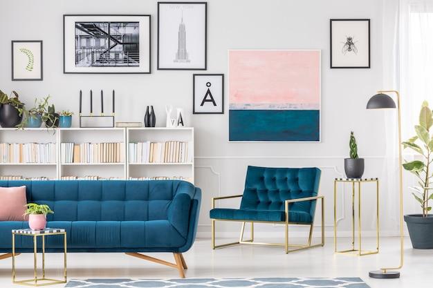 Artystyczne wnętrze salonu z niebieską sofą i fotelem, obrazami i złotymi stolikami