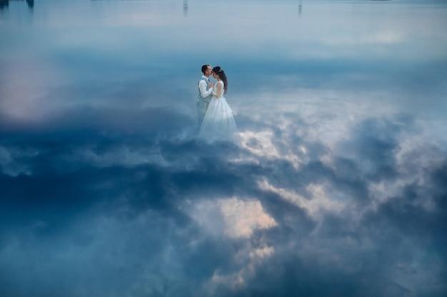 Artystyczne zdjęcie eleganckiego delikatnego stylowego pana młodego i panny młodej tańczy taniec weselny, podczas gdy mężczyzna całuje ładną panią. para ślub w koncepcji miłości