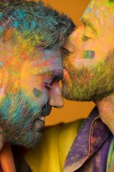Artystycznie malowany mężczyzna homoseksualny całuje chłopaka w czoło