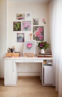 Artystyczny domowy stół roboczy biały jasny drewniany stół do malowania sztalugami i pięknymi dziełami sztuki z zawieszonymi na ścianie kwiatami i narzędziami do malowania. koncepcja kreatywności i hobby