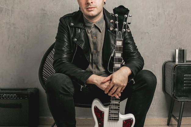 Artystyczny fotografia mężczyzna trzyma rocznik gitarę