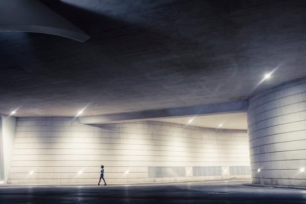 Artystyczny obraz samotnej kobiety spacerującej samotnie w miejskiej nocnej galerii - koncepcja bezpieczeństwa i niebezpieczeństwa