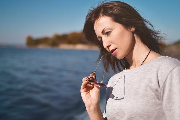 Artystyczny portret pięknej dorosłej kobiety na rzece morskiej na molo.
