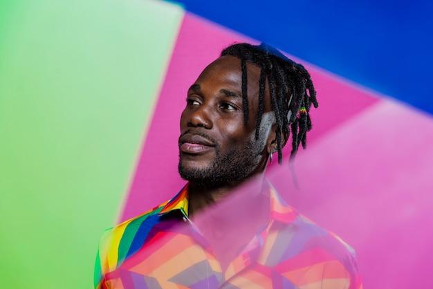 Artystyczny portret z żelowymi światłami. przystojny mężczyzna pozuje na kolorowym tle