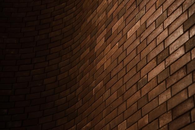Artystyczny wygląd zakrzywionej ściany z cegły gradientu cienia na tle architektury budynku.