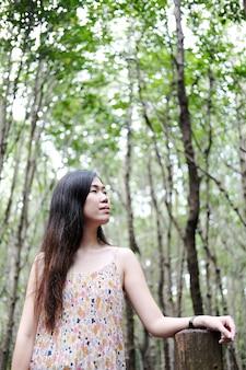 Asain dziewczyna uśmiecha się i siedzi na drewnianym moście w tropikalnym lesie namorzynowym