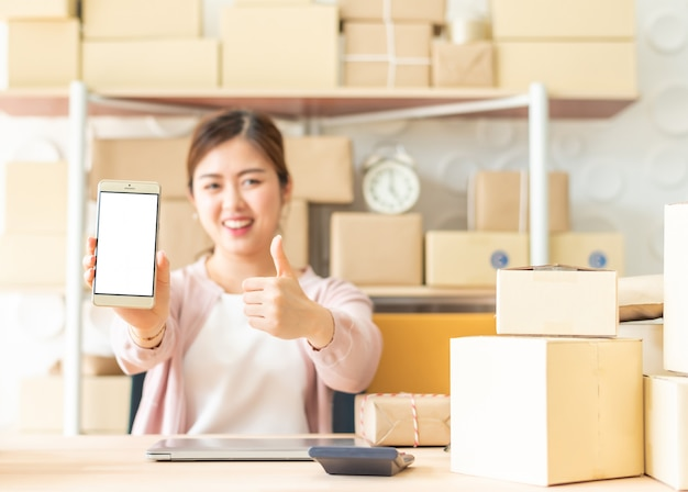 Asain kobieta pokazuje smartphone z kciukiem up