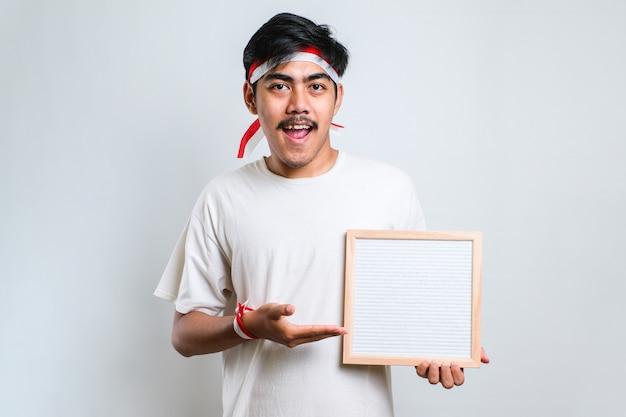 Asan mężczyzna noszący czerwono-białą opaskę na głowę trzymający pustą deskę wskazującą palcem na kamerę na białym tle