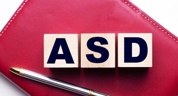 Asd składa się z drewnianych kostek, które stoją na bordowym notesie obok długopisu. pomysł na biznes