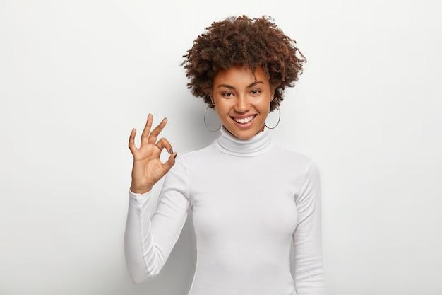 Asertywna, dobrze wyglądająca kobieta z krzaczastą fryzurą afro, pokazuje dobry gest