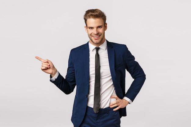 Asertywny charyzmatyczny blond biznesmen z włosiem, ubrany w klasyczny garnitur, wskazujący w lewo i uśmiechnięty, opowiadający o świetnym produkcie, reklamujący aplikację finansową, koncepcję biznesową