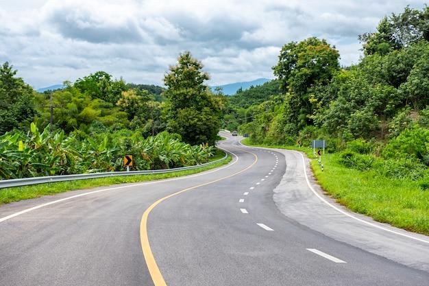 Asfaltowa autostrada wyginająca się z ciężarówką na wzgórzu