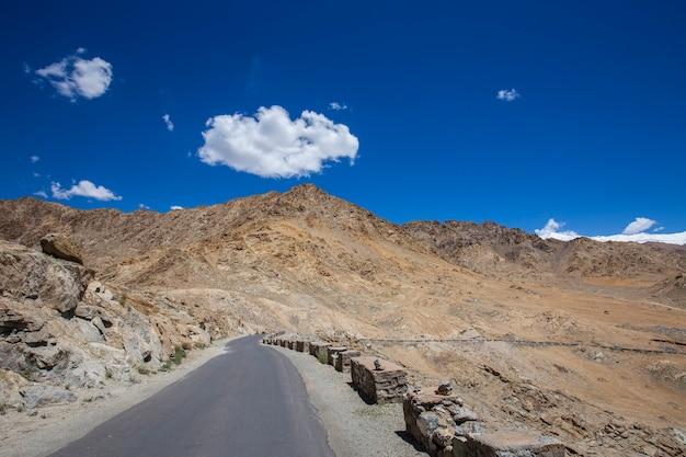 Asfaltowa droga w górach himalajach i biała chmura na błękitnym niebie w regionie ladakh, stan dżammu i kaszmir, północne indie