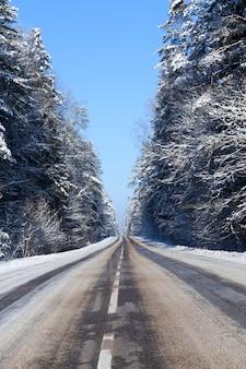 Asfaltowa droga z białymi znakami drogowymi pod śniegiem, część kolein po przejeżdżanych samochodach stopiła się, zimowy krajobraz