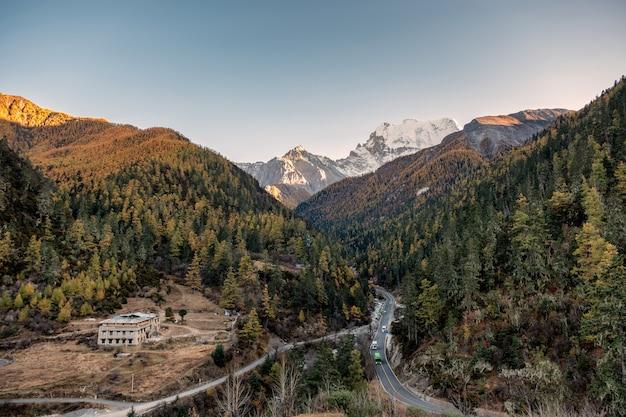 Asfaltowa droga z samochodami w jesieni dolinie z górą