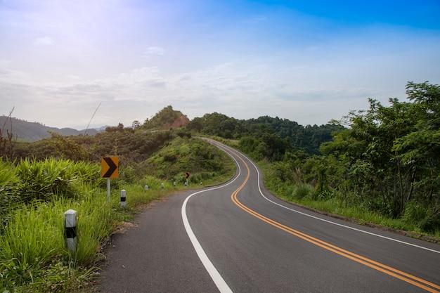 Asfaltowa droga z znakami wygina się w górach.