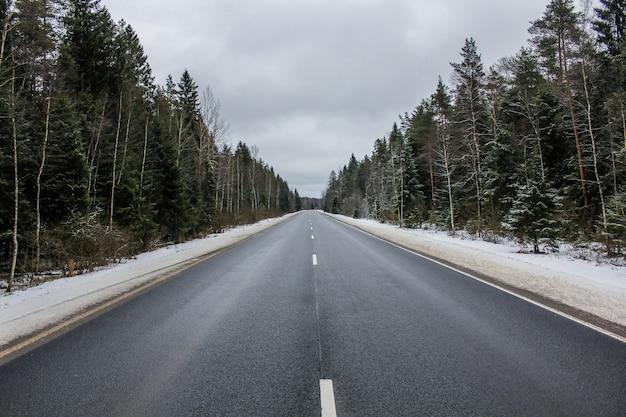 Asfaltowa droga zimowa przez las. rosyjska droga.