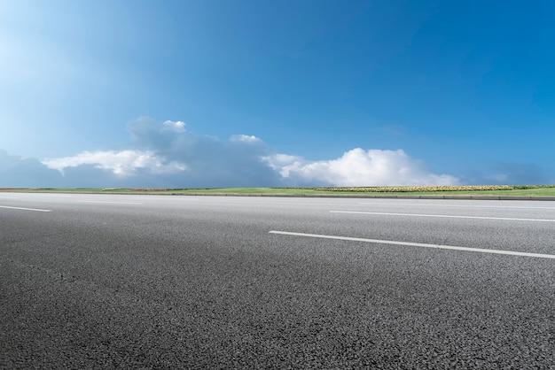 Asfaltowa linia horyzontu i błękitne niebo i biała chmura