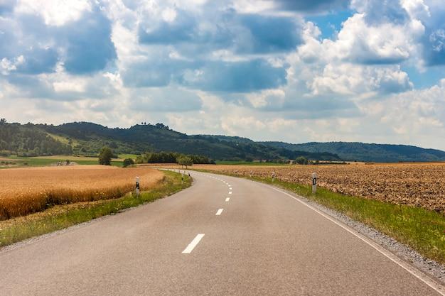 Asfaltowa wiejska droga w niemcy przez zielonego pola i chmur na niebieskim niebie w letnim dniu