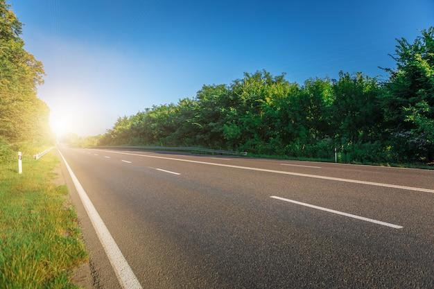 Asfaltowe autostrady i góry pod niebieskim niebem