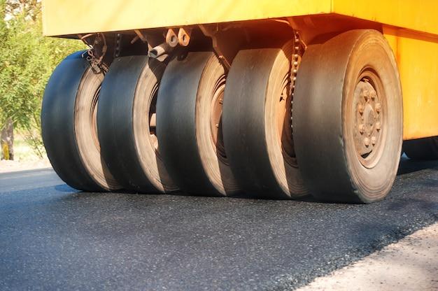 Asfaltowe nawierzchnie pracują na wibrującej rolce konstrukcji po naprawie drogi